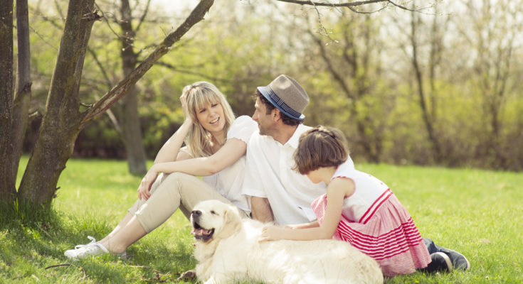 Family-sitting-in-park-with-dog
